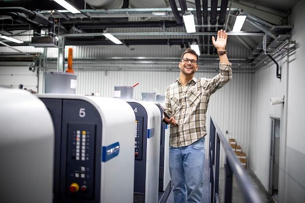 Designer gráfico acenando e verificando a produção na máquina de impressão offset na fábrica de impressão