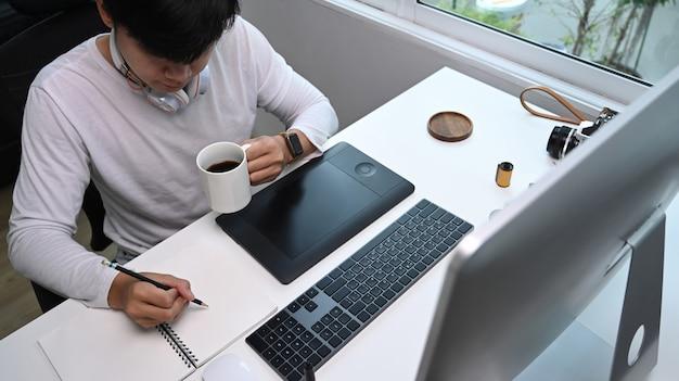 Designer gráfico anotando ideias em um caderno e tomando café na estação de trabalho