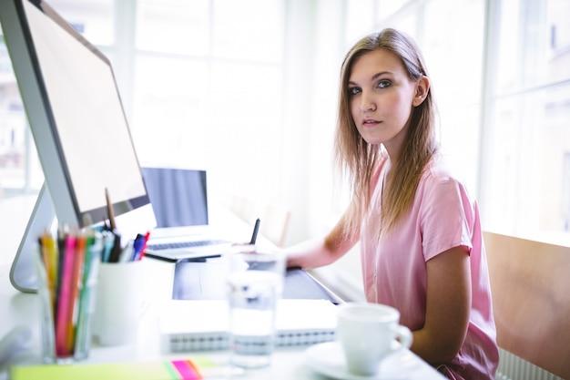 Designer gráfico confiante, sentado na mesa