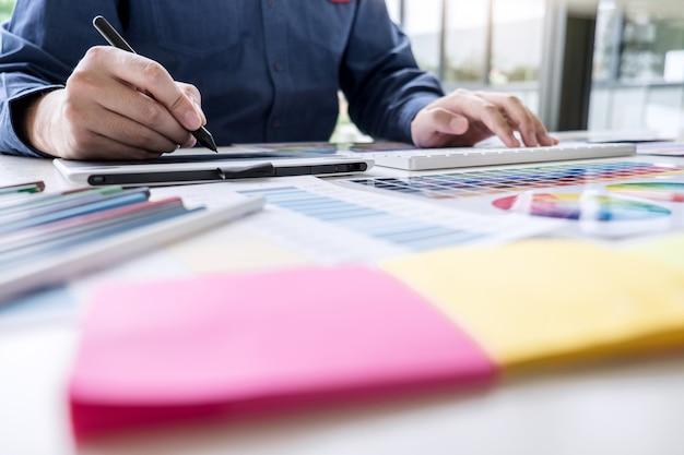 Designer gráfico criativo masculino, trabalhando na seleção de cor e amostras de cores, desenho na mesa digitalizadora no local de trabalho com ferramentas de trabalho e acessórios
