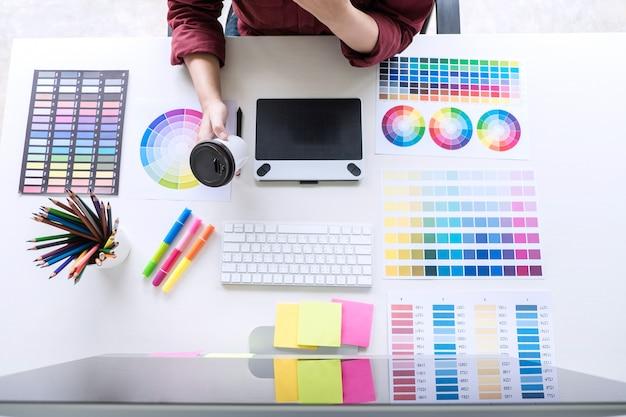 Designer gráfico criativo trabalhando na seleção de cores e desenho na mesa digitalizadora