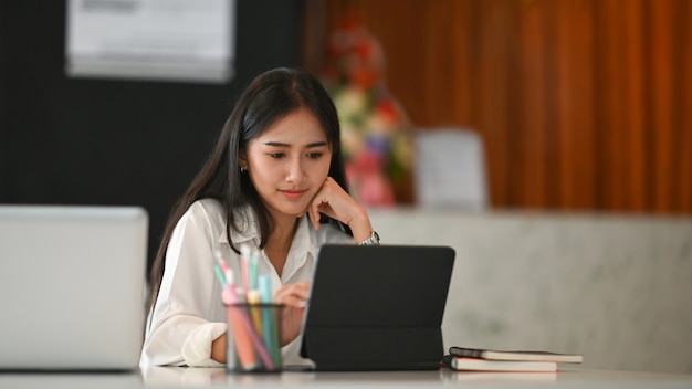 Designer gráfico de mulher jovem e atraente, trabalhando no escritório em casa e usando o computador tablet na mesa branca.