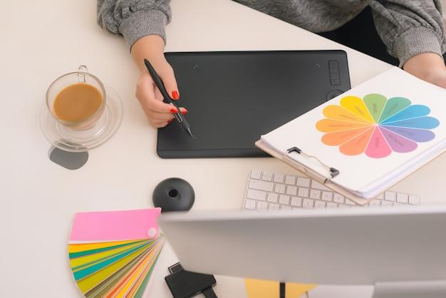 Designer gráfico desenhando em mesa digitalizadora no local de trabalho