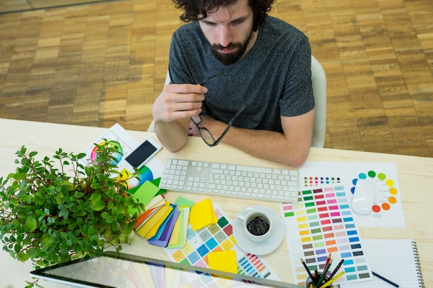 Designer gráfico do sexo masculino que olha o computador