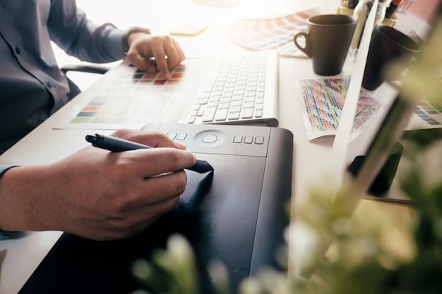 Designer gráfico está trabalhando usado mesa digitalizadora.