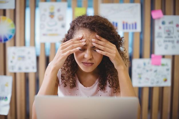 Designer gráfico feminino frustrado com localização de laptop na mesa