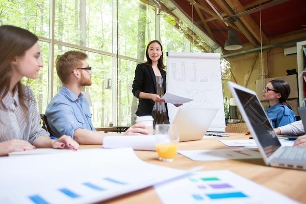 Designer gráfico feminino que discute a carta no quadro branco com os colegas de trabalho no escritório.