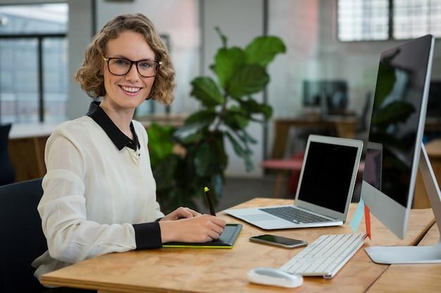 Designer gráfico feminino sentado à mesa