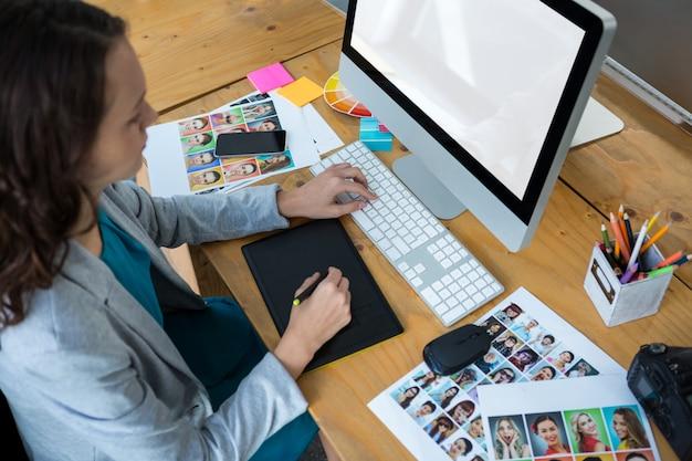 Designer gráfico feminino usando mesa digitalizadora na mesa