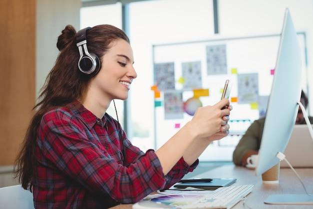 Designer gráfico feminino usando telefone celular