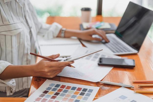 Designer gráfico freelancer de inicialização criativa, concentrando-se na tela do computador para projetar, codificar, programar aplicativos móveis a partir do layout do protótipo e da estrutura de arame.