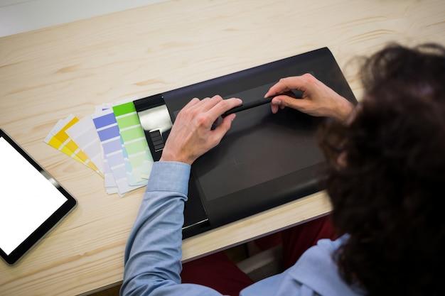 Designer gráfico masculino com mesa digitalizadora