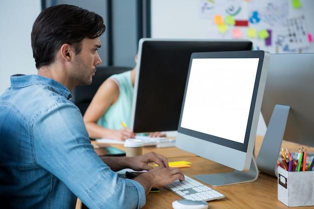 Designer gráfico masculino, usando a mesa digitalizadora na mesa