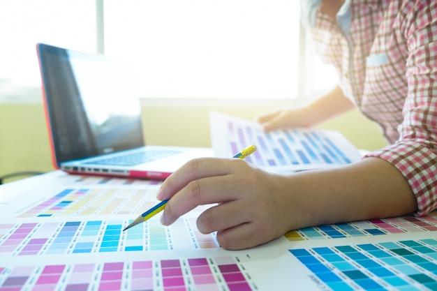 Designer gráfico no trabalho. amostras de amostras de cores.