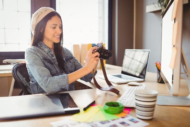 Designer gráfico olhando fotos na câmera digital