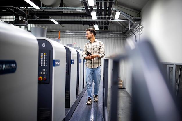 Designer gráfico profissional controlando o processo de impressão em uma máquina de impressão offset moderna