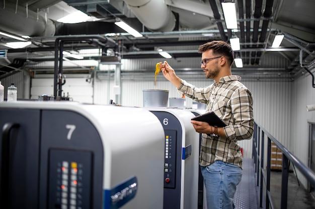 Designer gráfico profissional verificando valores de cor e tinta em uma máquina de impressão moderna