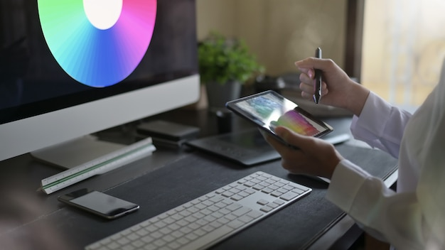 Designer gráfico que usa a tabuleta com seleção de cor, tiro da vista lateral.