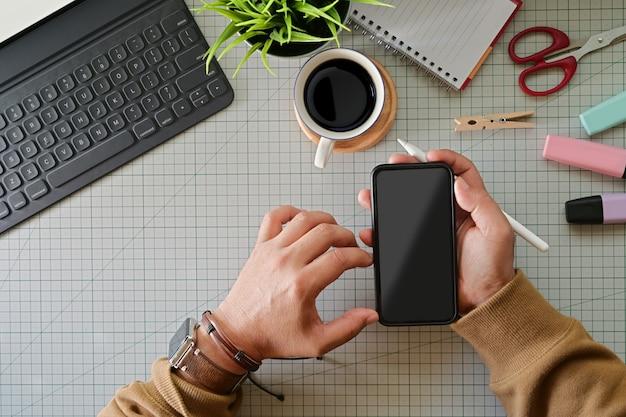 Designer gráfico, segurando, telefone móvel esperto, ligado, estúdio, topo, tabela