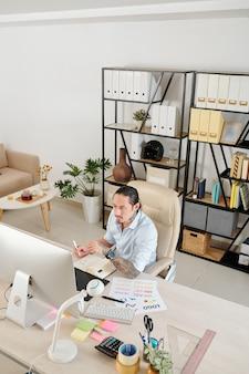 Designer gráfico sério e pensativo trabalhando em casa, verificando e-mails na tela do computador e fazendo anotações no planejador