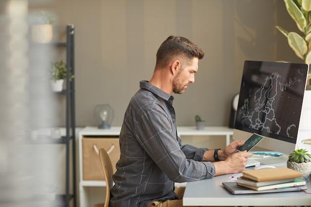 Designer gráfico sério sentado à mesa em frente ao computador e trabalhando no escritório