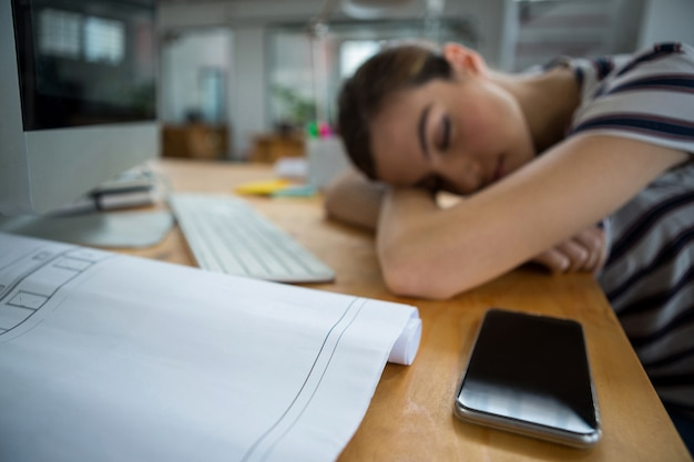 Designer gráfico sobrecarregado dormindo em sua mesa