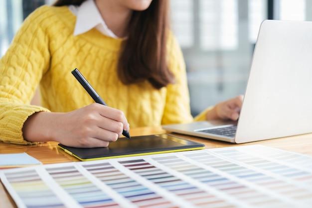 Designer gráfico trabalhando com amostras de cores para seleção.