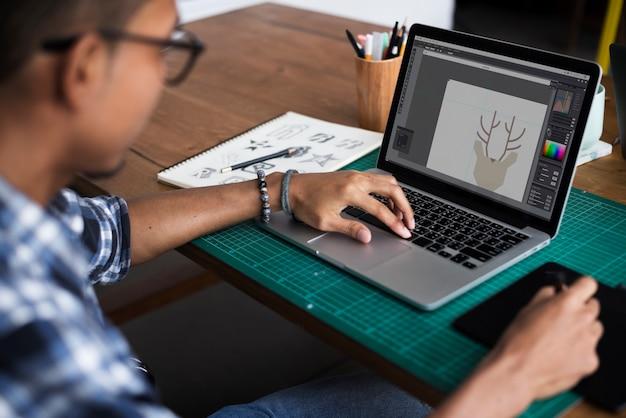 Designer gráfico, trabalhando com laptop e mousepad