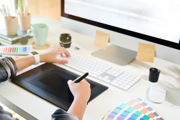 Designer gráfico, trabalhando em tablet digital.