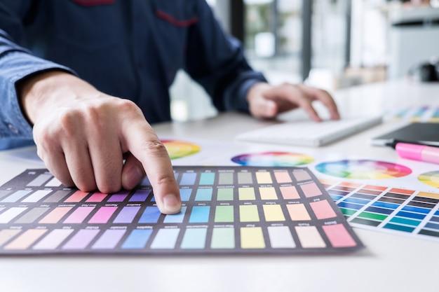 Designer gráfico trabalhando na seleção de cores e amostras de cores, desenho em mesa digitalizadora