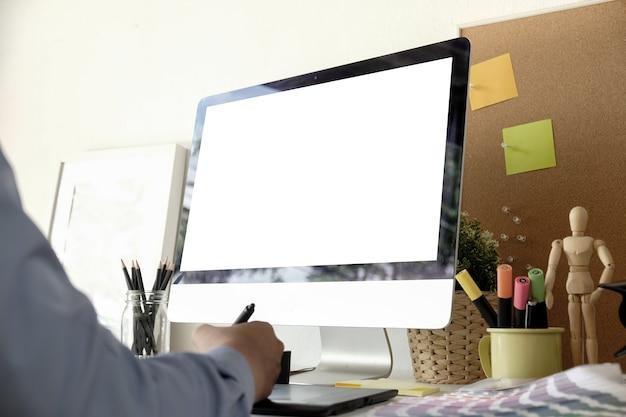 Designer gráfico, trabalhando no computador enquanto estiver usando o tablet gráfico na mesa no escritório