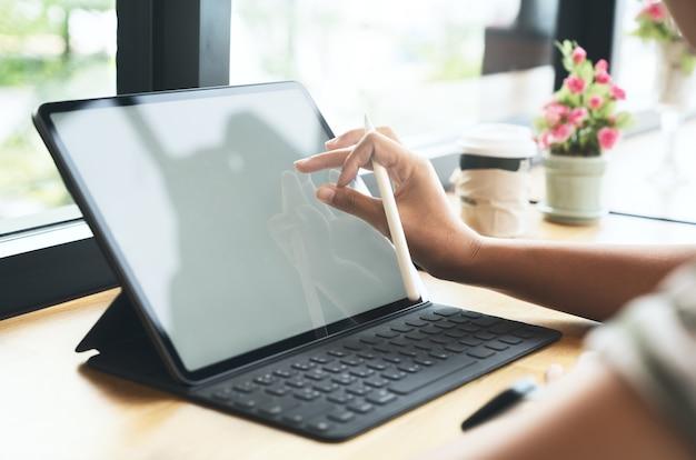 Designer gráfico usando caneta stylus no tablet