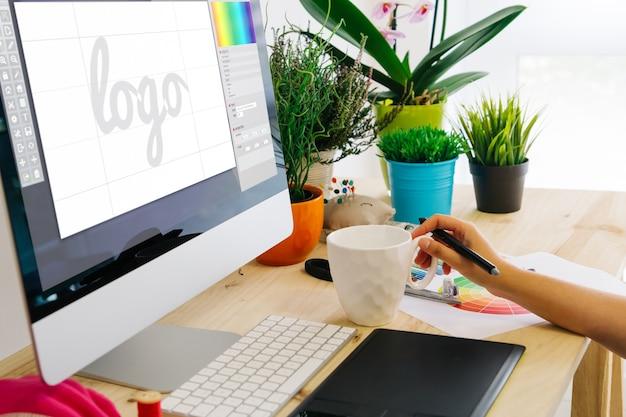 Designer gráfico usando caneta tablet para criar um logotipo.