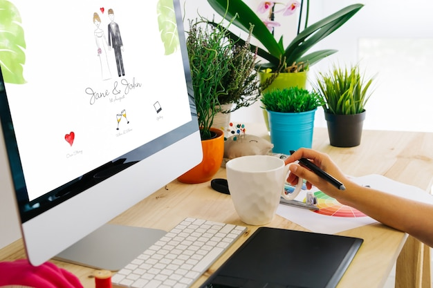 Designer gráfico usando caneta tablet para criar um site de casamento.