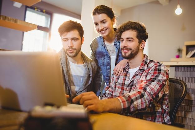 Designer gráfico usando laptop com seu colega de trabalho