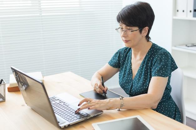 Designer gráfico usando seu tablet em um escritório luminoso.