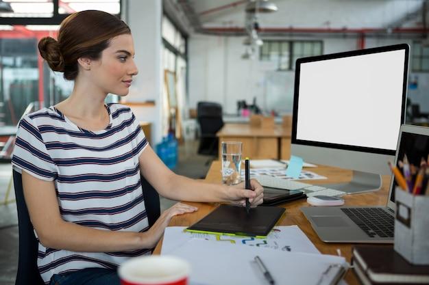 Designer gráfico usando tablet gráfico e desktop