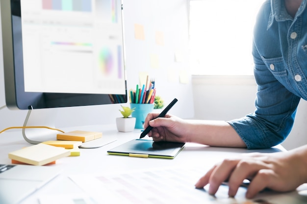 Designer gráfico usando tablet gráfico para trabalhar na mesa