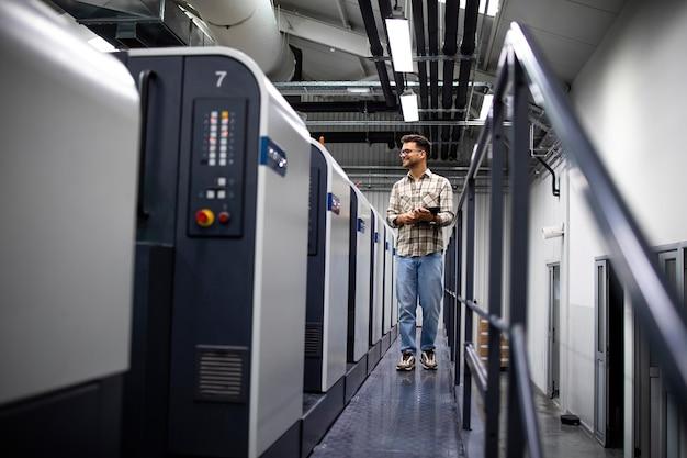 Designer gráfico verificando a qualidade de impressão e correspondência de cores em uma máquina de impressão offset moderna