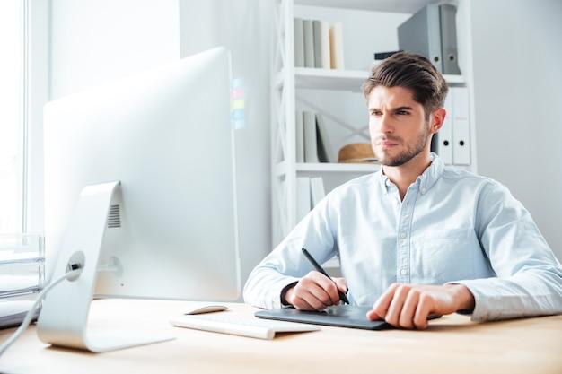 Designer jovem concentrado trabalhando com computador e tablet gráfico no local de trabalho