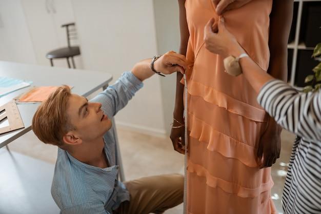 Designer loiro usando uma fita métrica enquanto está sentado de cócoras na frente da modelo