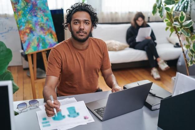 Designer masculino alegre com cabelos cacheados em traje casual se senta à mesa e projetando o conceito de camisas usando um laptop e uma caneta.