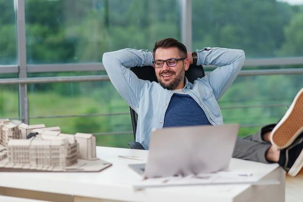 Designer masculino barbudo confiante de óculos sentado em uma pose relaxada no estúdio de design satisfeito com seu projeto