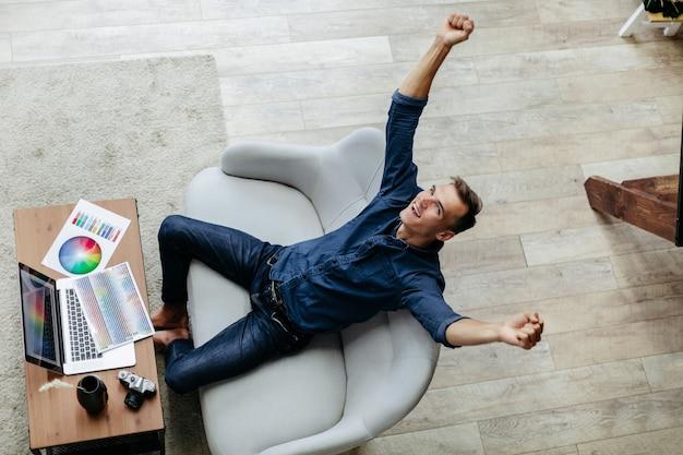 Designer masculino feliz sentado em sua mesa