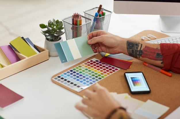 Designer masculino irreconhecível, trabalhando em paletas de cores Foto Premium