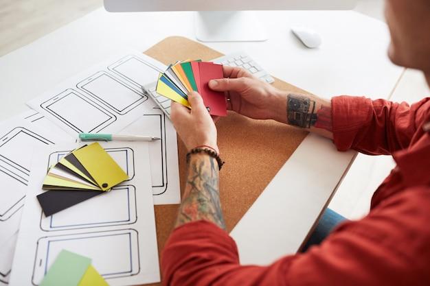 Designer masculino tatuado que escolhe a cor