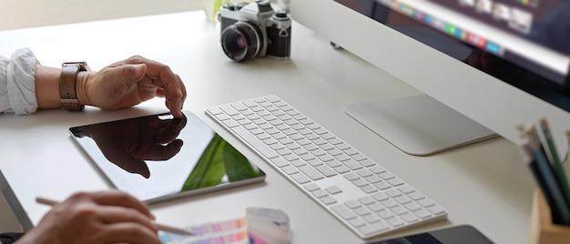Designer masculino, trabalhando com tablet digital, computador acima da mesa de escritório com smartphone, câmera e outros suprimentos