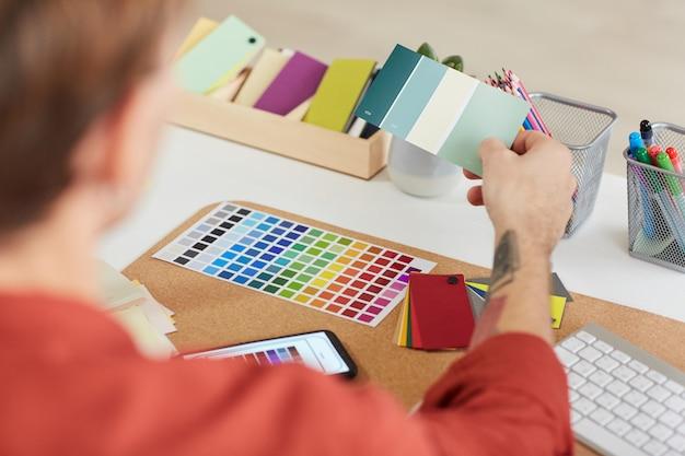 Designer masculino, trabalhando em paletas de cores