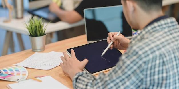 Designer masculino, trabalhando em seu projeto com tablet