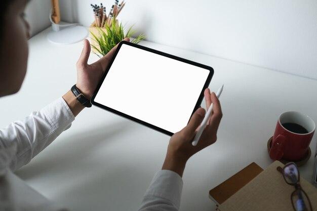 Designer masculino usando tablet digital de tela vazia com caneta stylus na mesa branca
